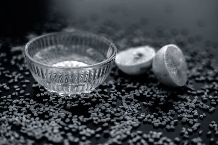 Famous natural method for dandruff on wooden surface in a glass bowl consisting of fenugreek seeds powder well mixed with lemon juice.With raw lemons and fenugreek seeds on the present on the surface. Reklamní fotografie