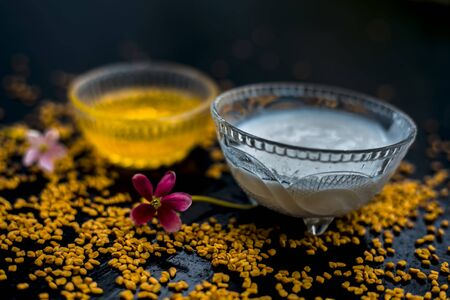 A famous natural method for dandruff on wooden surface in a glass bowl consisting of fenugreek seeds powder well-mixed with curd in a glass bowl.Along with raw curd and fenugreek seeds on the surface. Reklamní fotografie