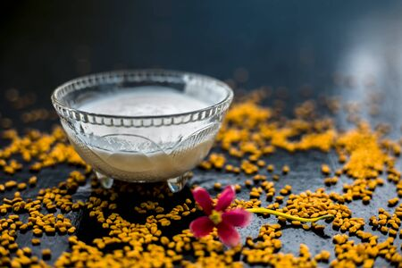 A famous natural method for dandruff on wooden surface in a glass bowl consisting of fenugreek seeds powder well-mixed with curd in a glass bowl.Along with raw curd and fenugreek seeds on the surface. Imagens