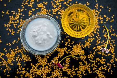 A famous natural method for dandruff on wooden surface in a glass bowl consisting of fenugreek seeds powder well-mixed with curd in a glass bowl.Along with raw curd and fenugreek seeds on the surface. Stok Fotoğraf