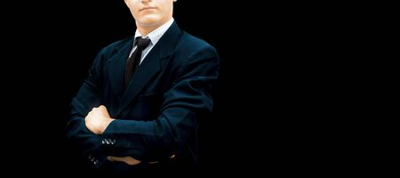 Half-length shot of a businessman wearing a dark blue colored jacket and a black necktie isolated on black and posing success with folded hands. Stok Fotoğraf