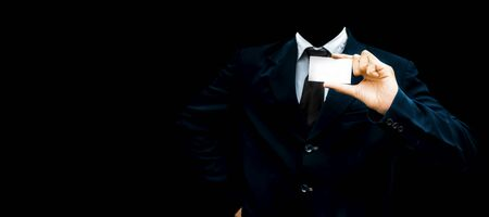 Unrecognizable faceless gentleman or seller holding white colored card in his hand wearing a dark blue colored suit with black necktie isolated on black.Concept of marketting. Stok Fotoğraf