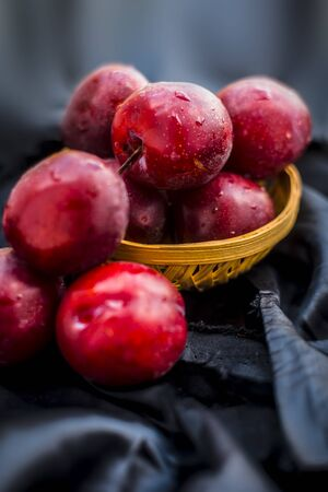 Raw organic red ripe plums in a brown-colored basket on black fabric on the wooden surface.