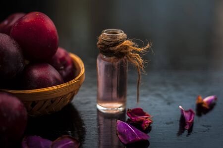 Raw organic red ripe plums in a brown-colored basket along with its extracted essential oil in a transparent glass bottle. Stok Fotoğraf