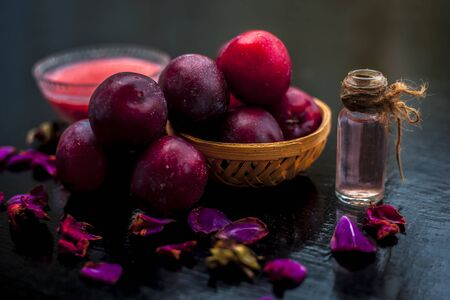 Raw organic red ripe plums in a brown-colored basket along with its extracted essential oil in a transparent glass bottle along with its paste in another glass bowl.