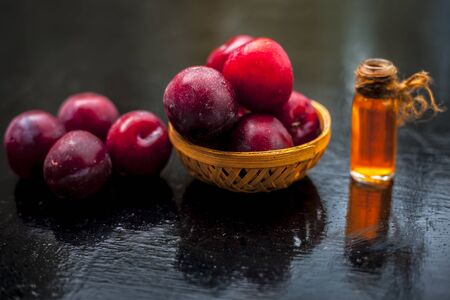 Raw organic red ripe plums in a brown-colored basket along with its extracted essential oil in a transparent glass bottle. 스톡 콘텐츠
