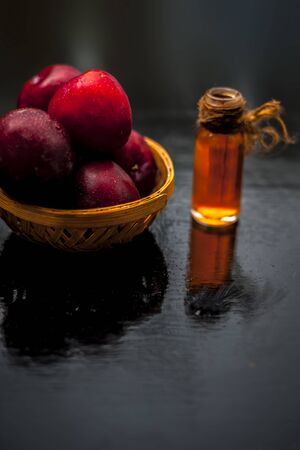 Raw organic red ripe plums in a brown-colored basket along with its extracted essential oil in a transparent glass bottle. 스톡 콘텐츠 - 132111223