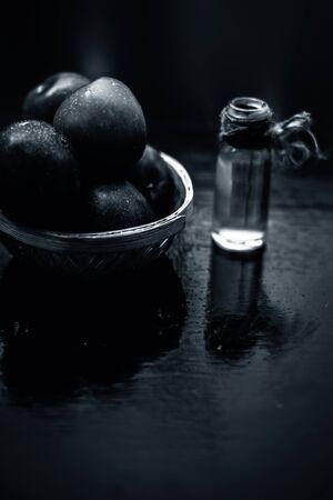 Prunes mûres rouges biologiques crues dans un panier de couleur marron avec son huile essentielle extraite dans une bouteille en verre transparent. Banque d'images