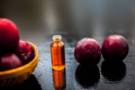 Raw ripe red plums along with its extracted essential concentration or essence in a glass bottle on a wooden surface. 스톡 콘텐츠