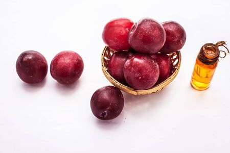 Raw organic red ripe plums in a brown-colored basket along with its extracted essential oil in a transparent glass bottle isolated on white. 스톡 콘텐츠