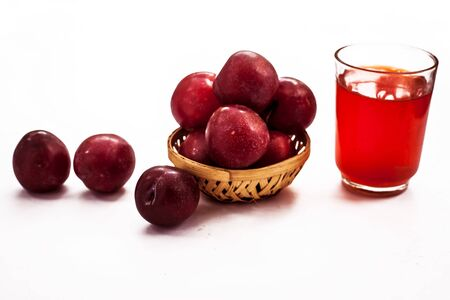Raw organic red ripe plums in a brown-colored basket along with its extracted tincture or extracted water in a glass isolated on white. 스톡 콘텐츠 - 132111236