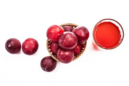 Raw organic red ripe plums in a brown-colored basket along with its extracted tincture or extracted water in a glass isolated on white.