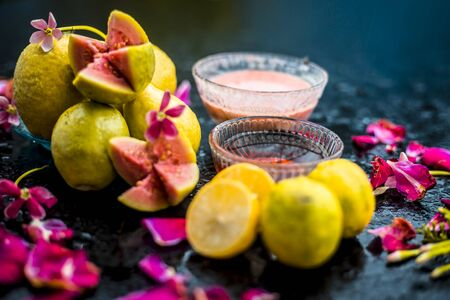 The easiest method to cure acne and scars with guava face mask consisting of guava pulp, honey, and some lemon juice.With ingredients on wooden surface in a glass bowl.;