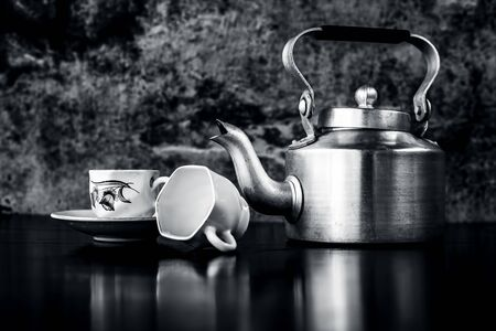 Still life with antique kettle and glass set on the black colored shining surface with black and white gothic colors.Still life concept.
