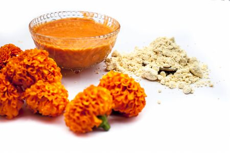 Marigold flower face mask consisting of some besan or chickpea flour well mixed with milk in a glass bowl isolated on white along with marigold flowers and some flour.Horizontal shot. Stock fotó