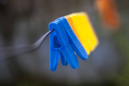 Colorful clothespin or clothes peg or clothes clip on a clothesline with a blurred background.