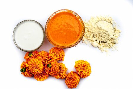 Marigold flower face mask consisting of some besan or chickpea flour well mixed with milk in a glass bowl isolated on white along with marigold flowers and some flour.Horizontal top shot. Stock fotó