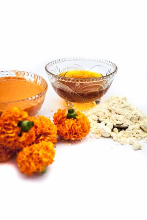 Marigold face mask for dry skin isolated on white consisting of marigold, honey, and some chickpea flour or gram flour in a glass bowl along with entire of its constituents.