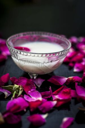Fresh milk cream or milk lotion in a glass bowl on black surface along with some rose petals spread on the surface.Vertical shot.