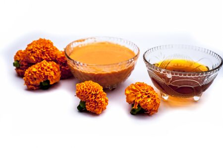 Marigold flower face mask isolated on white in a glass bowl consisting of marigold flower and honey well mixed. With all constituents.