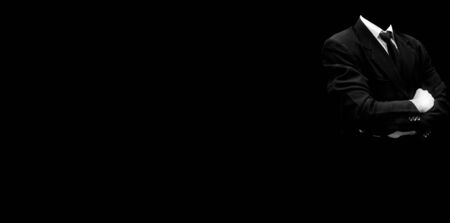 Faceless unrecognizable brave businessman with crossed hands standing against black background with attitude to face any difficult challenge in work. Wide-angle high-resolution image. Stock Photo