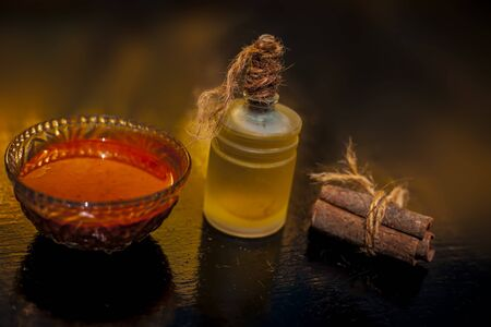 Cinnamon powder, honey and olive oil hair mask in a glass bowl on a wooden surface with gold lights isolated. Along with raw cinnamon stick, honey & olive oil present on the surface. Horizontal shot.