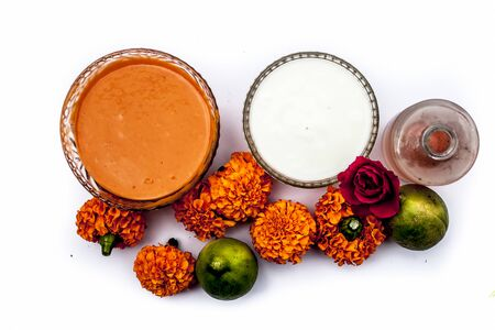 Marigold face mask for dry skin on wooden surface i.e., marigold flowers, milk cream, rose water and some lemon juice well mixed together in a glass bowl. Shot along with raw flowers,cream,and lemons. Banco de Imagens