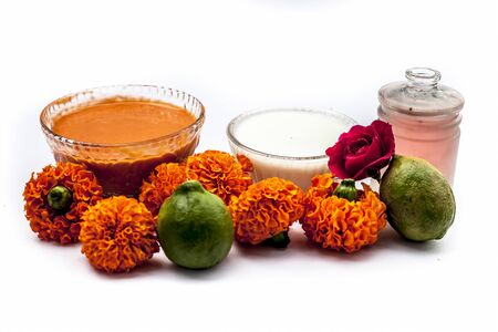 Marigold face mask for dry skin on wooden surface i.e., marigold flowers, milk cream, rose water and some lemon juice well mixed together in a glass bowl. Shot along with raw flowers,cream,and lemons. Stok Fotoğraf - 137632234
