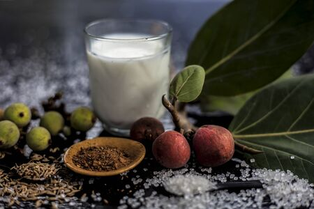 Close up of best ayurvedic remedy for Premature Ejaculation on the wooden surface consisting of Banyan fruit powder, sugar and cumin seeds well mixed in a glass. Shot of all the ingredients. 版權商用圖片