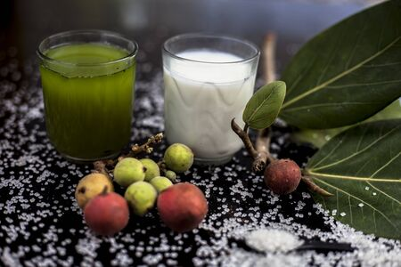 Best drink remedy to control weight on the black glossy wooden surface consisting of Banyan Tree fruit juice well mixed with milk and some sugar. Shot of all ingredients on surface.Horizontal shot.