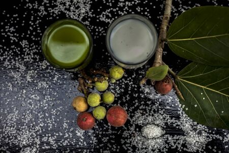 Best drink remedy to control weight on the black glossy wooden surface consisting of Banyan Tree fruit juice well mixed with milk and some sugar. Shot of all ingredients on the surface.Top shot. 版權商用圖片
