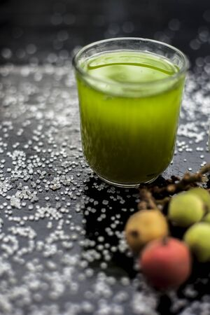 Best drink remedy to control weight on the black glossy wooden surface consisting of Banyan Tree fruit juice well mixed with milk and some sugar. Shot of all ingredients on surface.Vertical shot.