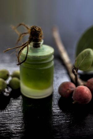 Close up shot of essential banyan tree oil in a transparent glass bottle along with some banyan fruit and its leaf on a black glossy wooden surface. Vertical shot.