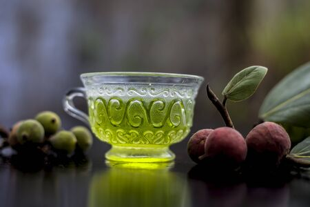 Detoxifying herbal ayurvedic banyan tree tea or Indian wishing tree tea in transparent glass cup along with some ripe and raw banyan fruit on a black glossy surface with blurred background.