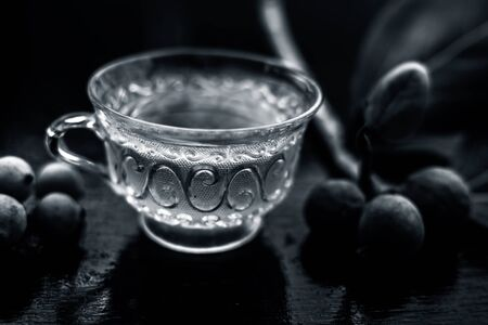Detoxifying herbal ayurvedic banyan tree tea or Indian wishing tree tea in transparent glass cup along with some ripe and raw banyan fruit on a black glossy surface. Horizontal shot. 版權商用圖片