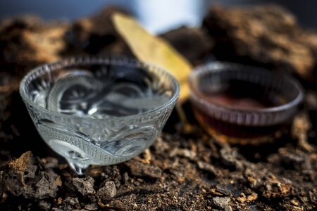 Home remedy for sexually transmitted diseases on a black glossy surface consisting of Banyan tree bark powder well mixed with water and some honey. Horizontal high angle shot.