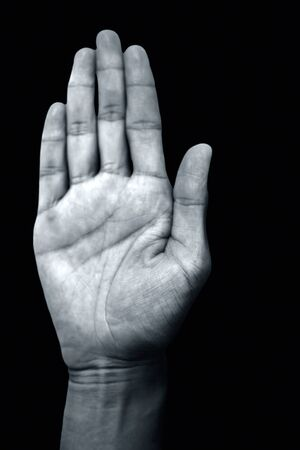 Isolated pair of hands of a male teenager on black background doing Abhayaprada Yoga Mudra.Vertical shot.