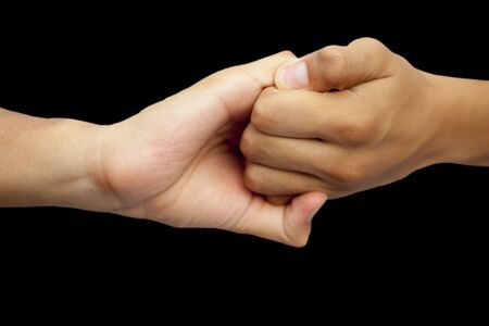 Isolated hands of male teenagers doing Ganesha Yoga Mudra with two hands-on black background.Horizontal shot. Stock Photo