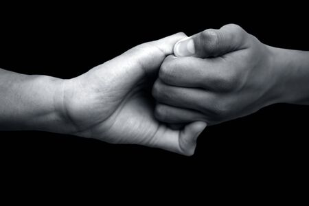 Isolated hands of male teenagers doing Ganesha Yoga Mudra with two hands-on black background.Horizontal shot.