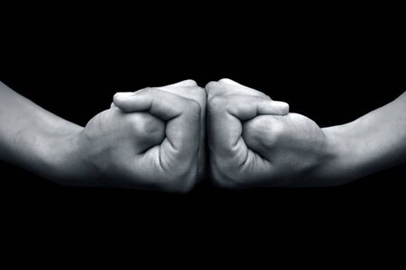 Isolated pair of hands of a male teenager on black background doing Brahma yoga mudra.Horizontal shot.