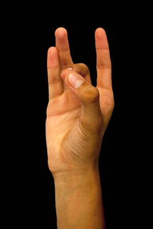 Isolated hand of a male teenage boy doing Shuni or Shoonya Yoga Mudra by joining his tip of middle finger to the tip of the thumb on a black colored background.Vertical shot.