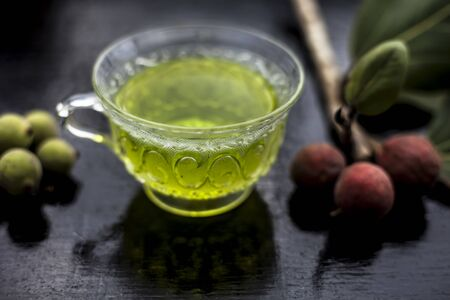 Close up shot of herbal floral and beneficial Banyan tree tea in a glass cup on a wooden surface along with its leaves and fruit.