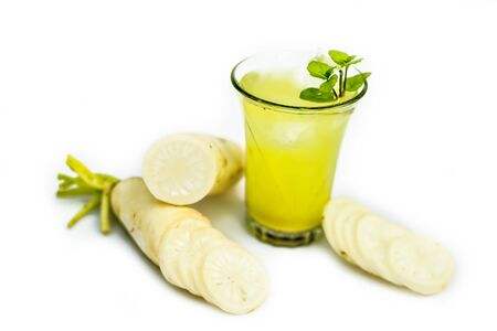 Close up shot of fresh daikon juice in a glass isolated on a white background along with some sliced daikon and some lemon. Horizontal shot of daikon juice with some mint leaves on it.