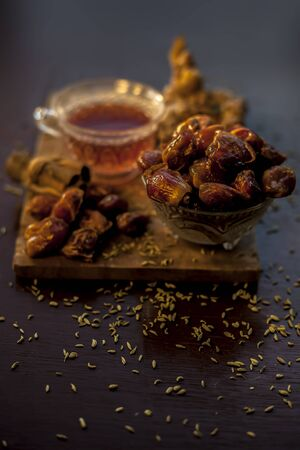 Dates tea in transparent glass cup along with some fennel seeds, cinnamon sticks and ginger well mixed and put together in tea.The vertical well lit upshot of dates tea in a transparent glass cup. Archivio Fotografico