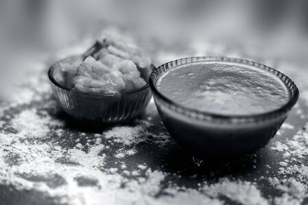 Close up of Indian desi winter drink Bajri Rabb winter drink or Bajri ki rabdi/rabri in a glass bowl along with some raw spread pearl millet flour and jaggery. On a brown wooden surface. Stock Photo