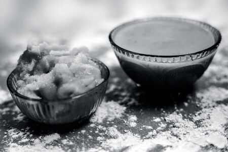 Close up of Indian desi winter drink Bajri Rabb winter drink or Bajri ki rabdi/rabri in a glass bowl along with some raw spread pearl millet flour and jaggery. On a brown wooden surface.