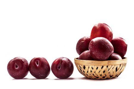Prugne mature rosse organiche crude in un cesto di colore marrone isolato su bianco per un facile utilizzo per qualsiasi scopo.