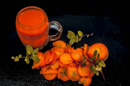 Close up of Carrot juice or Daucus carota subsp. sativus juice for dieting and weight loss with mint and carrot pieces for garnish On the black glossy surface. Horizontal high angle shot.;