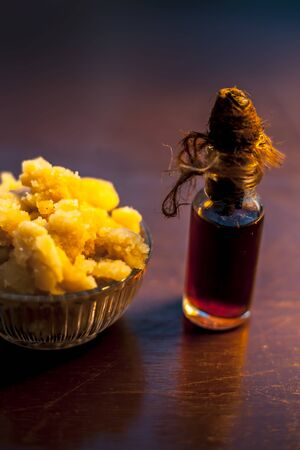 Close up of glass cup full of raw jaggery or gud or palm jaggery and its extracted oil in a glass bottle used for oil pulling in ayurvedic dental treatment. Vertical shot.