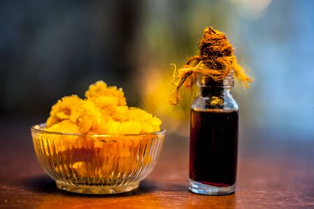 Close up of glass cup full of raw jaggery or gud or palm jaggery and its extracted oil in a glass bottle used for oil pulling in ayurvedic dental treatment. Horizontal shot.